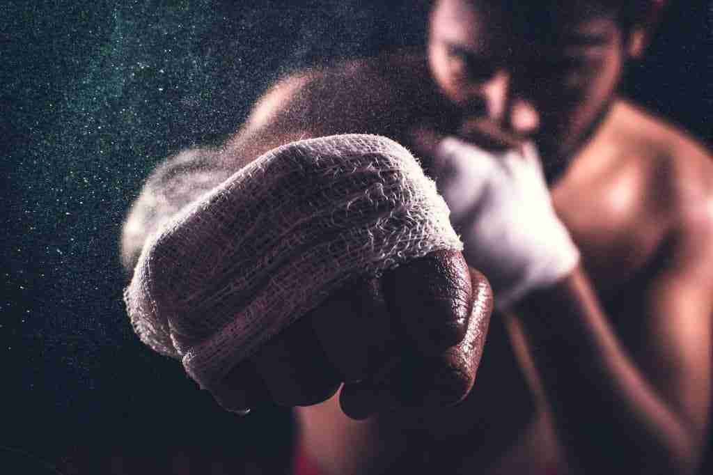 Man in white hand wraps punching towards the camera
