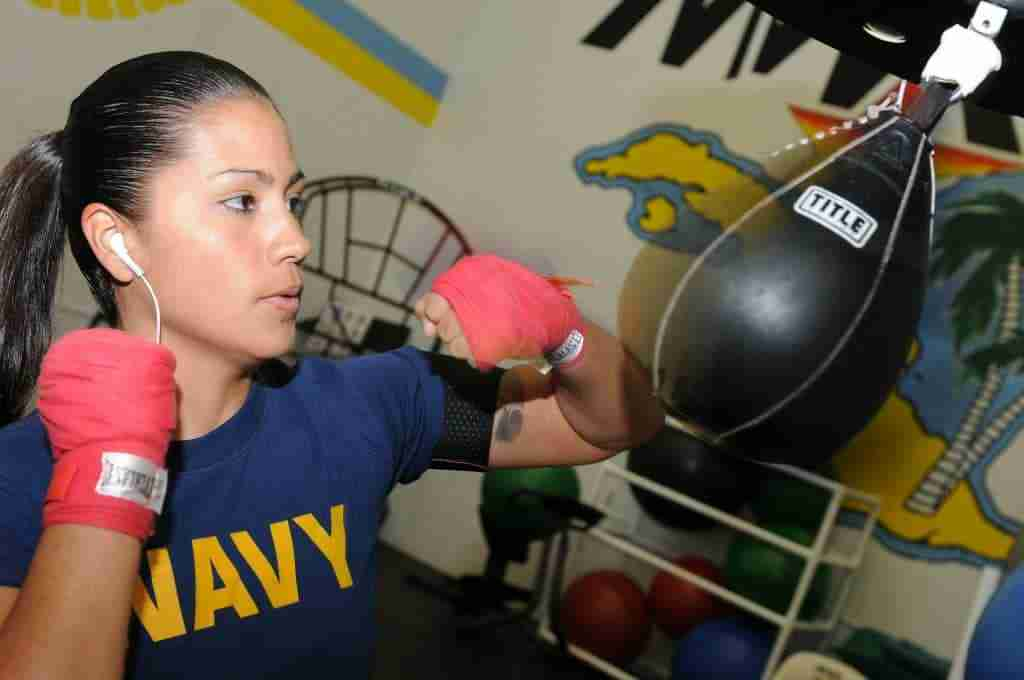 Woman with headphones punching speed bag in boxing gloves