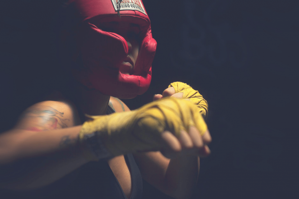 Woman punching with yellow hand wraps