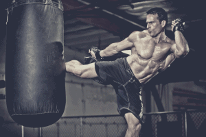 Man kicking a heavy bag