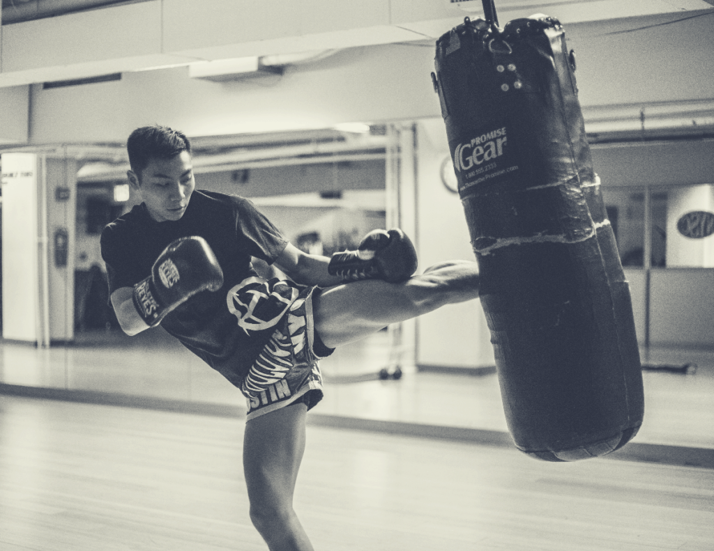 Asian man in gym, wearing boxing gloves, kicking heavy bag