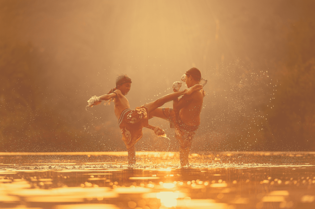 Two young boys doing Muay Thai in a lake